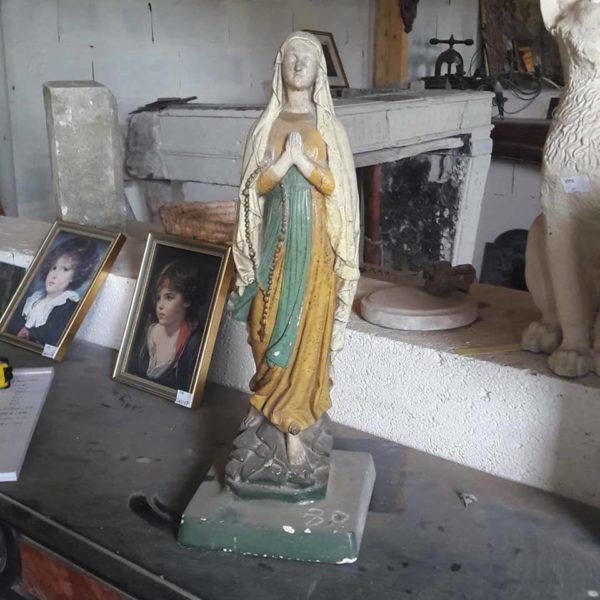 Statuette de la Vierge en plâtre coloré. La Vierge est représentée les mains jointes et en mouvement.